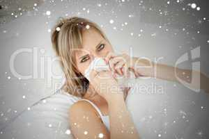 Composite image of sick blonde woman blowing lying on her bed