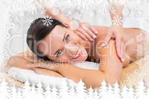 Beautiful brunette enjoying a shoulder massage smiling at camera