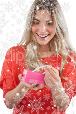 Composite image of blonde woman discovering necklace in a gift b