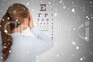 Composite image of brunette woman making an eye test