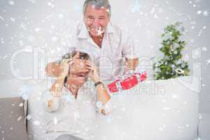 Composite image of old man hiding eyes of his wife for a gift