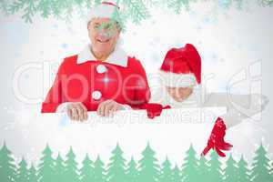 Festive older couple smiling and holding poster