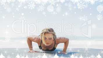 Composite image of fit blonde in plank position on the beach