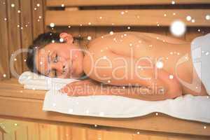 Happy brunette lying down in a sauna