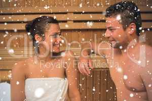 Smiling couple relaxing in a sauna and chatting