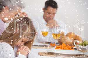 Composite image of little girl saying grace with family