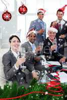 Manager and his team with novelty christmas hat toasting at a pa