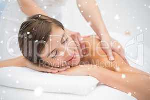 Attractive young woman receiving shoulder massage at spa center