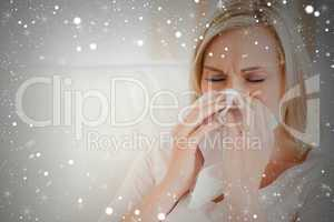 Composite image of ill woman blowing her nose