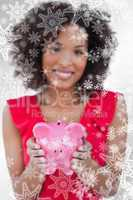 Composite image of piggy bank being held by a brunette woman