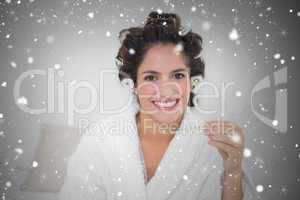Composite image of smiling natural brunette holding thermometer