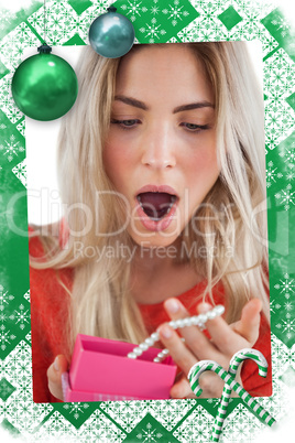 Shocked woman discovering necklace in a gift box