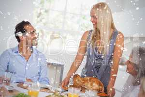 Composite image of happy wife bringing turkey to the table