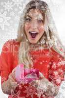 Composite image of surprised woman discovering necklace on a box