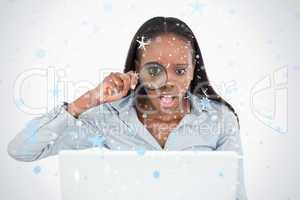 Businesswoman using a magnifying glass to look at her laptop