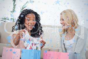 Two laughing women look at clothes they bought