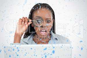 Businesswoman using a magnifying glass to look at her notebook