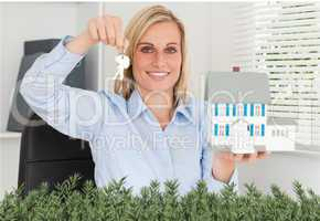 Gorgeous businesswoman presenting model house and keys looks int