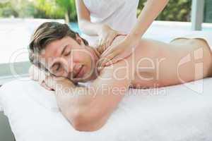 Handsome man receiving shoulder massage at spa center