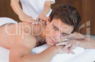 Man receiving shoulder massage at spa center