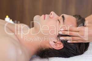 Man receiving head massage at spa center