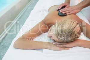 Woman receiving stone massage at health farm