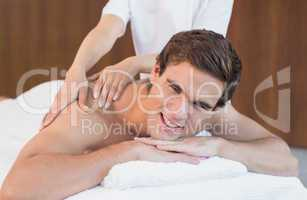 Young man receiving shoulder massage at spa center