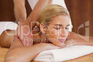 Woman receiving shoulder massage at spa center
