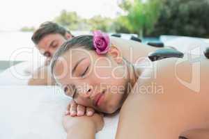 Couple enjoying stone massage at health farm