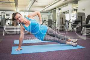 Fit brunette doing pilates on exercise mat