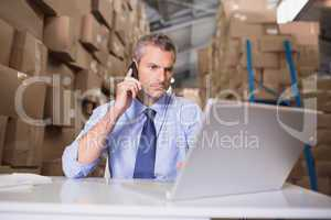 Warehouse manager using cellphone and laptop