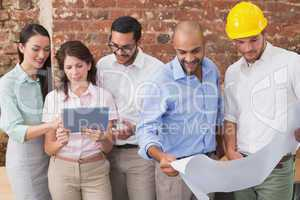 Architect colleagues working on blueprints and digital tablet