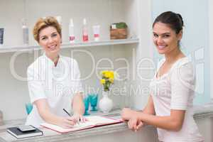 Pretty beautician smiling with client