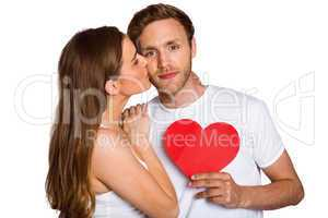 Woman kissing man as he holds heart