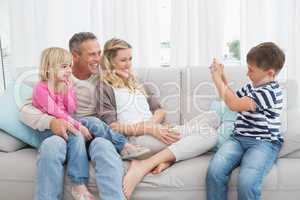 Son taking a photo of his family
