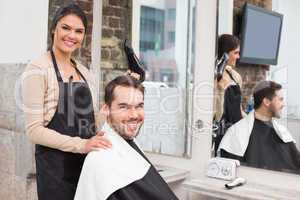 Hair stylist and client smiling at camera