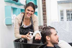 Hair stylist putting conditioner in mans hair