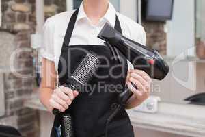 Hairdresser holding brush and hairdryer