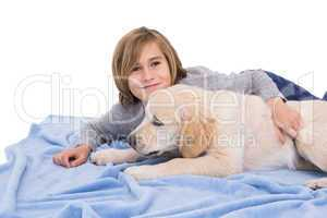 Child rubbing his dog lying on a blanket