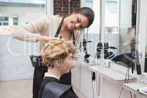 Happy hairdresser cutting a customers hair