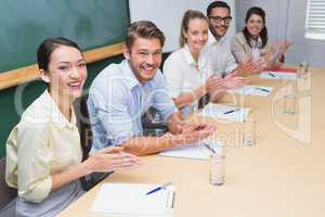 Business team sitting in a row clapping at camera