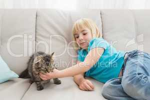 Little girl lying on the couch stroking her cat