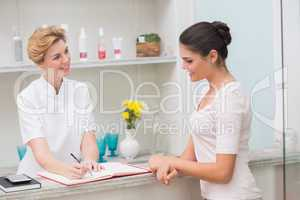 Pretty beautician talking with client