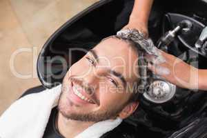 Hair stylist washing mans hair