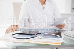 Doctor sitting at her desk with laptop and files