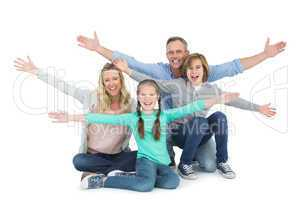 Cheering family with two children sitting on the floor