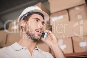 Worker using cellphone in warehouse