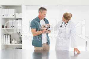 Owner holding rabbit with vet