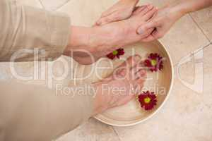 Pedicurist cleansing customer feet