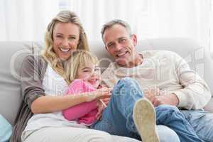 Happy parent tickling their cute daughter on the couch